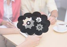 La gente alla tavola con la compressa dietro il grafico grigio dell'ingranaggio e della nuvola Fotografia Stock