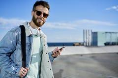 La gente alle vie di passeggiata del lavoro in città facendo uso del telefono e del wifi Immagini Stock