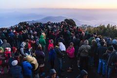 La gente apretada está esperando la primera luz en el amanecer del día del ` s del Año Nuevo con la montaña y la niebla en fondo  Imagen de archivo libre de regalías