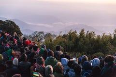 La gente apretada está esperando la primera luz en el amanecer del día del ` s del Año Nuevo con la montaña y la niebla en fondo  Fotos de archivo libres de regalías