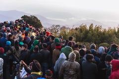 La gente apretada está esperando la primera luz en el amanecer del día del ` s del Año Nuevo con la montaña y la niebla en fondo  Imagenes de archivo
