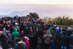 La gente apretada está esperando la primera luz en el amanecer del día del ` s del Año Nuevo con la montaña y la niebla en fondo  Fotografía de archivo