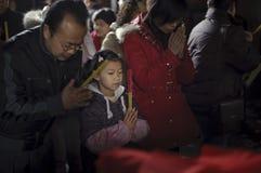 La gente apretada se arrodilla abajo y rogando en templo Imagen de archivo
