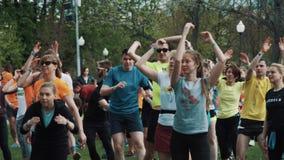 La gente aprieta en el parque de la ciudad que hace los ejercicios, corriendo en un lugar, día de verano almacen de metraje de vídeo