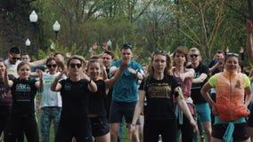 La gente aprieta en el parque de la ciudad que hace los enchufes de salto con las manos rised, calentando almacen de video
