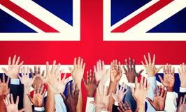 La gente arma aumentado y una bandera de Reino Unido Fotos de archivo