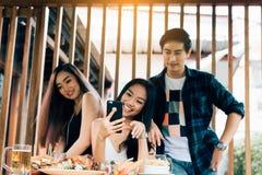 La gente asiática del grupo que se encuentra en el restaurante con goza el reír junta fotografía de archivo libre de regalías
