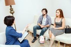 La gente astuta e bella sta sedendo davanti allo psicologo e sta esaminandola Medico sta parlando con loro e Immagine Stock