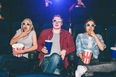La gente asustada y asustada está mirando película en cine Son que se sientan y que parecen directos Todo el mundo tiene a Imagen de archivo