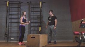 La gente atractiva de los deportes está haciendo saltos de la caja mientras que se resuelve en gimnasio almacen de metraje de vídeo