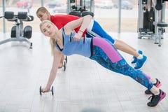 La gente atractiva de los deportes se está resolviendo con pesas de gimnasia en gimnasio foto de archivo libre de regalías