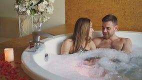 La gente atractiva joven es de abrazo y que habla en bañera que burbujea con espuma en balneario moderno del día Relación románti metrajes