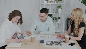 La gente attraente ed alla moda lavora in un ufficio moderno La donna bionda felice graziosa dà le istruzioni importanti lei stock footage