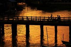 La gente attraversa il ponte di legno nel tramonto, Nyaungshwe, Myanmar fotografie stock