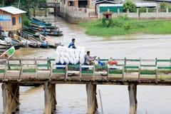 La gente attraversa il ponte di legno, Nyaungshwe, Myanmar immagini stock libere da diritti