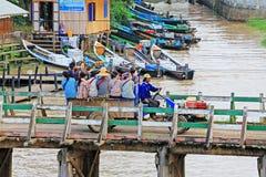 La gente attraversa il ponte di legno, Nyaungshwe, Myanmar immagini stock