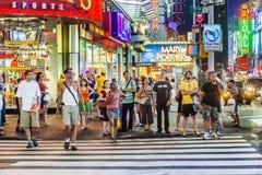 La gente attraversa la via vicino al Times Square Fotografie Stock