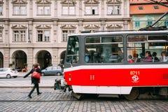 La gente attraversa le piste del tram sulla via Immagini Stock