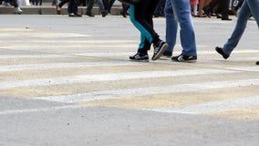 La gente attraversa la strada ad un passaggio pedonale stock footage