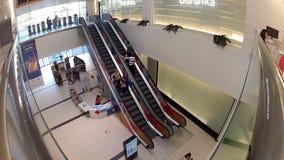 La gente aumenta e va giù sulla scala mobile nel centro commerciale della città del centro commerciale stock footage