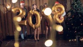 La gente balla vicino ad un albero di Natale con 2018 numero a forma di palloni stock footage