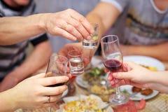 La gente bebe en la tabla, vidrios del tintineo fotografía de archivo