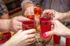La gente bebe en la tabla, vidrios del tintineo fotografía de archivo libre de regalías