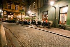 La gente bebe fuera del café en el edificio histórico Imagen de archivo libre de regalías