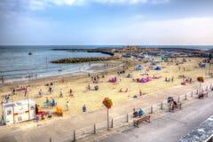 La gente britannica della costa di Lyme Regis Dorset della spiaggia e del porto gode del sole della fine dell'estate Fotografia Stock