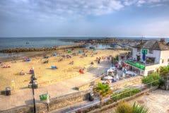 La gente britannica della costa di Lyme Regis Dorset gode del sole della fine dell'estate Fotografia Stock