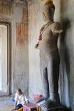 La gente camboyana que se sienta para ruega con la estatua de la imagen de Vishnu Foto de archivo