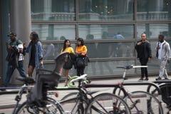 La gente camina abajo de la calle en el mediodía de trabajo Imagen de archivo libre de regalías