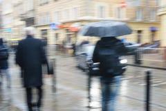 La gente camina abajo de la calle en lluvia Foco borroso Imágenes de archivo libres de regalías