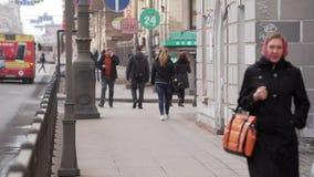La gente camina en calle a lo largo de fachadas de los edificios, camino con los coches móviles y autobuses almacen de metraje de vídeo