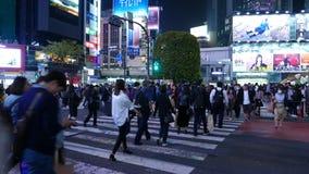 La gente camina en el cruce de Shibuya Luz de neón brillante, paso del tren cerca, Tokio, Japón metrajes