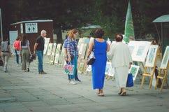 La gente camina en el parque en la celebración del día del ` s de la ciudad y mira la exposición del PA foto de archivo libre de regalías
