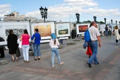 La gente camina en el puente de Patriarshy en Moscú y mira las fotografías Imagen de archivo