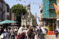 La gente camina en la calle delante de la cruz de Chichester el 12 de agosto de 2016 en Chichester, Reino Unido Fotos de archivo