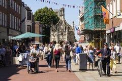 La gente camina en la calle delante de la cruz de Chichester el 12 de agosto de 2016 en Chichester, Reino Unido Imagenes de archivo