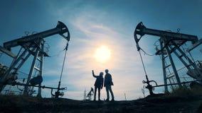 La gente camina en un campo petrolífero con las torres de perforación almacen de metraje de vídeo