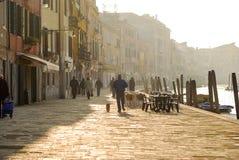 La gente camina junto a un canal en su manera de trabajar en Venecia, Italia temprano por la mañana foto de archivo