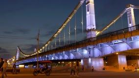 La gente camina a lo largo del terraplén cómodo en el puente con las luces coloreadas brillantes metrajes