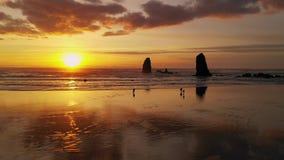 La gente camina la playa del cañón mientras que las olas oceánicas pacíficas reflejan resplandor de la puesta del sol almacen de metraje de vídeo