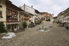 La gente camina por la calle de la ciudad medieval de Gruyeres, Suiza Imagenes de archivo