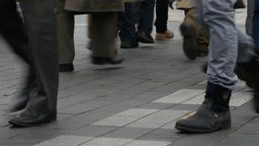 La gente camina a través de un camino por el paso del paso de peatones o de cebra metrajes