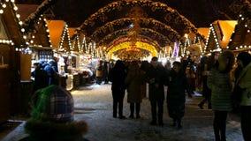 La gente camina y hace compras en un mercado de la Navidad de la calle metrajes