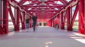 La gente camina y las sombras cambian en el Skyway simétrico rojo 4K UHD Timelapse metrajes