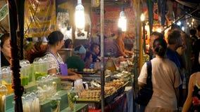 La gente cammina all'alimento asiatico nazionale della via nel mercato di notte sulla spiaggia di Jomtien archivi video