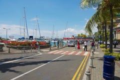 La gente cammina dalla via nella regione di lungomare di Caudan di Port Louis, Mauritius immagini stock libere da diritti