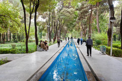 La gente cammina lungo la fossa con acqua in un parco con gli alberi antichi alti Fotografia Stock